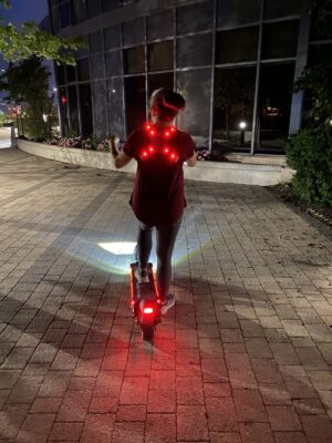 Rider on an E-Scooter with a lit up X-vest and helmet.