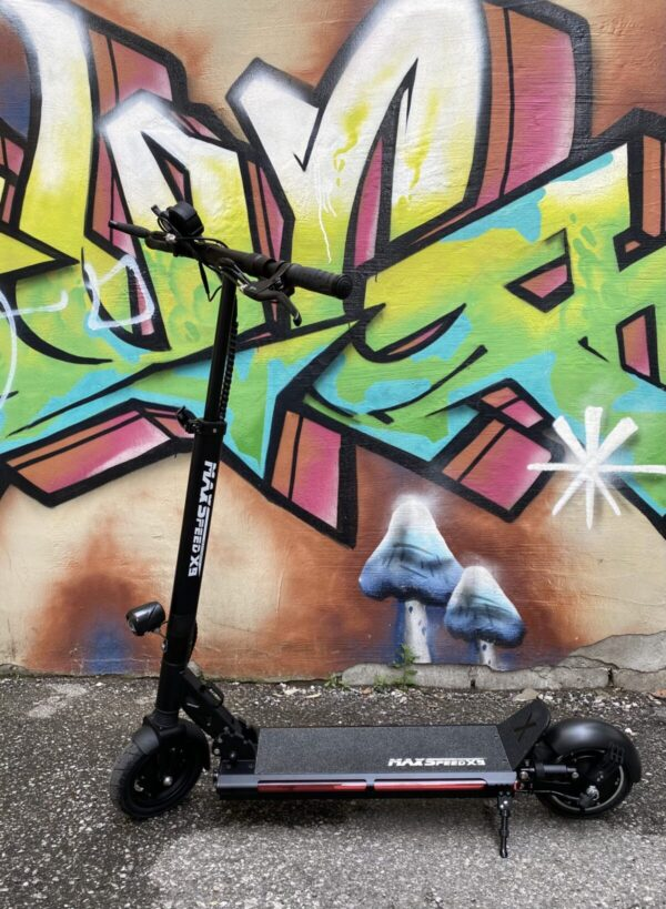 The Maxspeed X9S E-Scooter in front of graffiti.