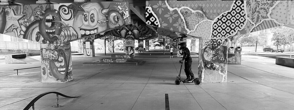 Man riding E-Scooter near graffiti covered walls.