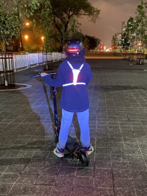 Person wearing a lit up Y-Vest at night.